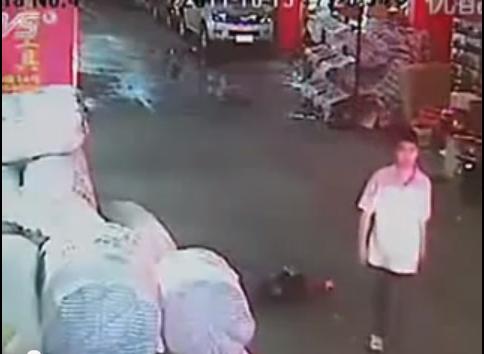 Bild från en film från en övervakningskamera i en kinesisk stad som visar hur 18 personer passerade en två-åring som kördes över av flera bilar.