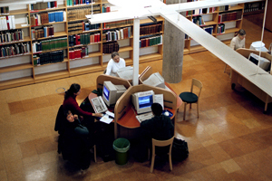Studenter runt ett studiebord på ett bilbliotek.