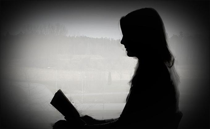 Läsande kvinna i profil.