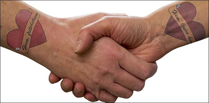"""Handskakning. På den ena handleden en tatuering med hjärta och text """"Hem fritidshem"""", på den andra """"Hem ljuva hem""""."""