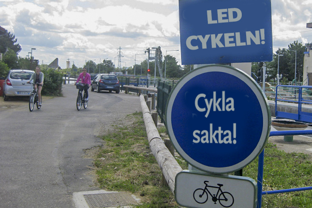 Skyltar på cykelbana. Skylt 1: Led cykeln. Skylt 2: Cykla sakta