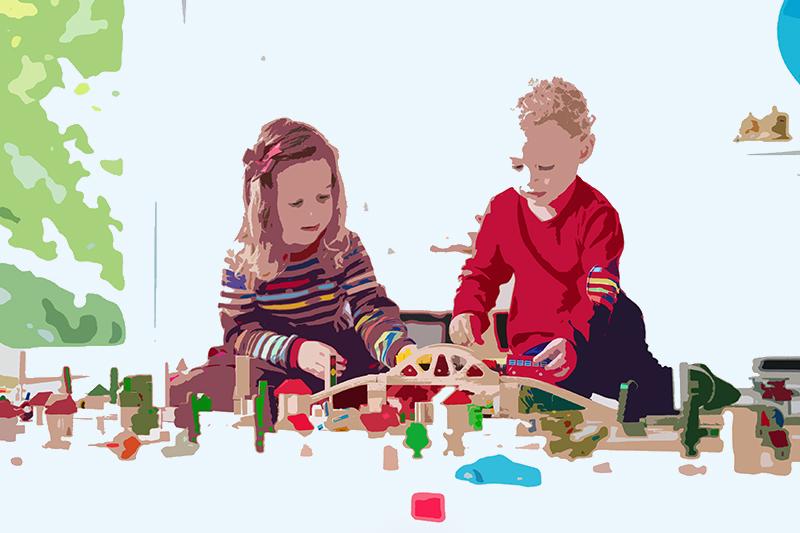 Två förskolebarn som leker på golvet.