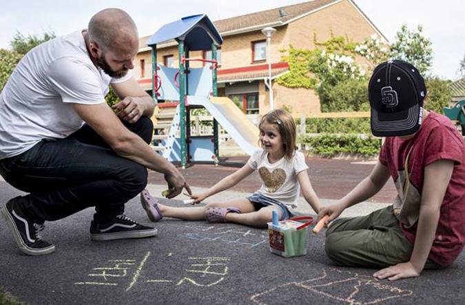 Lärare i fritidshem med två barn på skolgård.